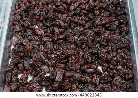 Selective focus,Raisins dried on metal baking tray with sunlight outdoor for displace moisture.
