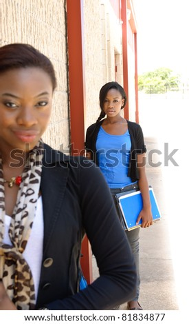 Selective focus shot of young African college student in background with her teacher in the foreground.