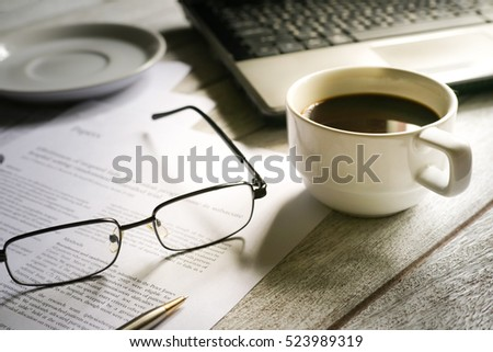 Selective focus table : eyeglass , mobile phone, laptop, note book and pen on the wooden table.working Business concept with effect light added