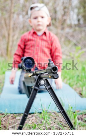 Selective focus to the barrel of a large hunting rifle mounted on a tripod with a small boy kneeling behind it on a mat in wooded countryside - stock photo