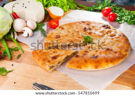 Selective Focus Traditional vegetable closed pie on the table. Composition of ingridients.