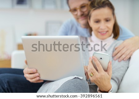 Selective focus view of happy senior couple sitting on sofa looking at laptop and phone together at home