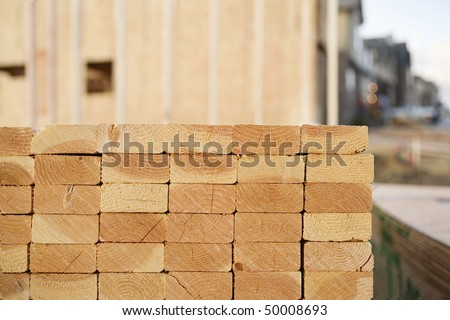 Selective focus view of the end of a stack of 2x4 boards at a construction site, with a framed building and finished construction in the background. Horizontal shot. - stock photo