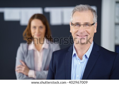 Selective focus view on smiling business man in blue suit jacket and eyeglasses while woman with folded arms stands behind him - stock photo