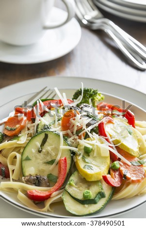 Selective focus was used on this pasta primavera made with fettuccine, basil, squash, zucchini, red bell pepper, broccoli, carrots, mushrooms and peas and topped with freshly shredded parmesan cheese. - stock photo