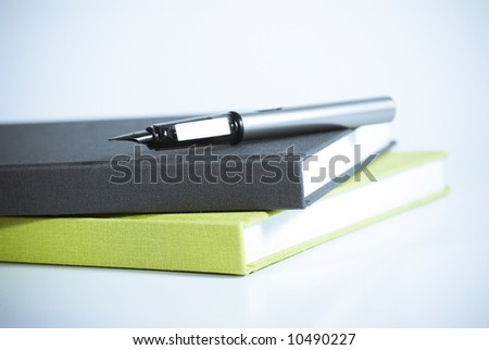 selective mood shot of modern pen and books - stock photo