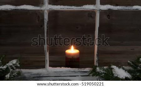 Selective view of a glowing candle through a snow covered window with fir branches.