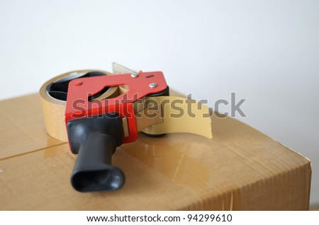 Self-adhesive tape dispenser on brown cardboard box - stock photo