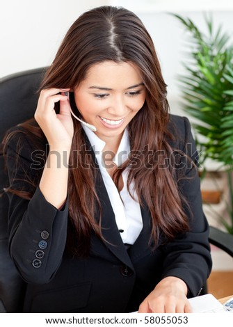 Self-assured asian businesswoman wearing headphones siiting at her disk in the office - stock photo