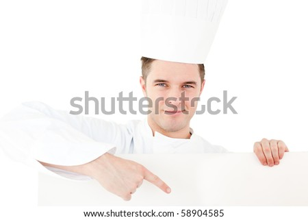 Self-assured caucasian male cook holding a placard showing on it against white background - stock photo