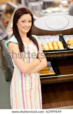 Self-assured female cook smiling at the camera in front of her bakery at work - stock photo