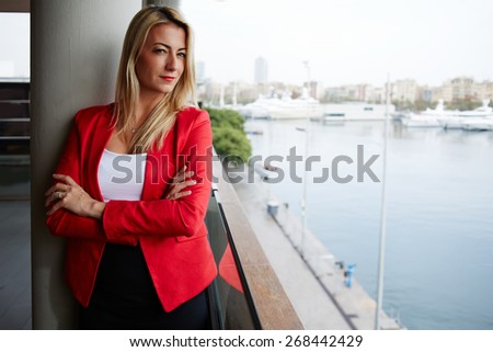 Self confidence concept, attractive businesswoman looking to you while standing at office balcony with beautiful seaport view on background, female executive with crossed arms looking to the camera - stock photo