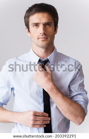 Self-confident and handsome. Confident young man in formalwear adjusting his necktie and looking at camera while standing against grey background - stock photo