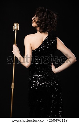 Self-confident gorgeous young female vocalist in shiny black evening dress prepare to sing during live concert holding golden vintage microphone - stock photo
