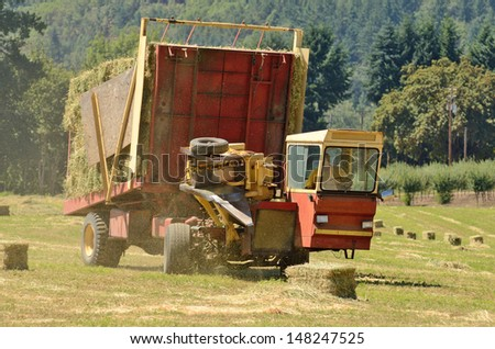 Self contained hay bale wagon picking up bales of alfalfa from a farm field - stock photo