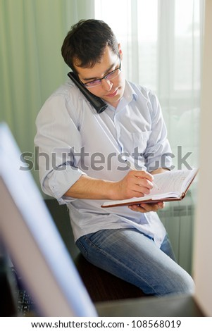 Self-employed man working at home. Talking on phone
