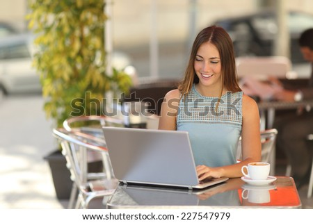 Self employed woman or student working in a restaurant terrace in the street with an unfocused background - stock photo