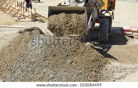 Self loading concrete mixer  taking gravel and sand to bucket - stock photo