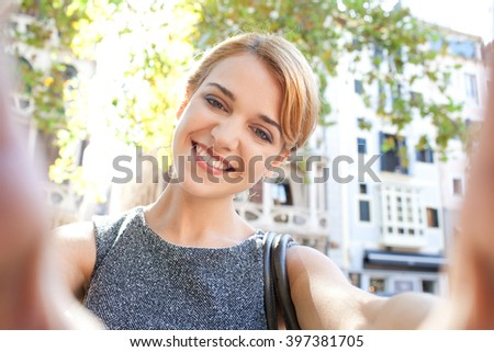 Self portrait of a young smart tourist woman holding a smart phone, taking selfies joyfully smiling on holiday, sunny city outdoors. Travel lifestyle, using technology connectivity, fun exterior. - stock photo