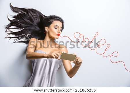 Self-portrait of glamor sexy brunette girl with the golden phone. Woman lying on the floor, pouting duck. From the mouth of red woolen thread goes inscription Selfie. - stock photo