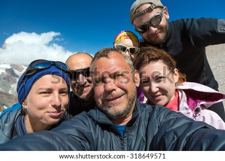 Self Portrait of Group of Merry Climbers Faces of Five People Men and Women Young and Older Expressing Fun and Joy Blue Sky Background - stock photo