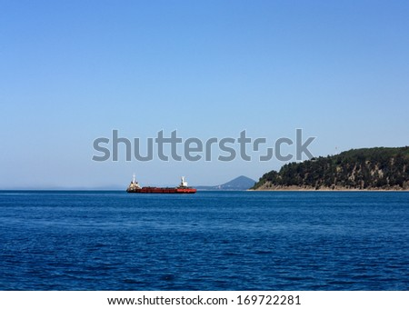 Self-propelled barge at sea in the roads waiting to enter the seaport - stock photo