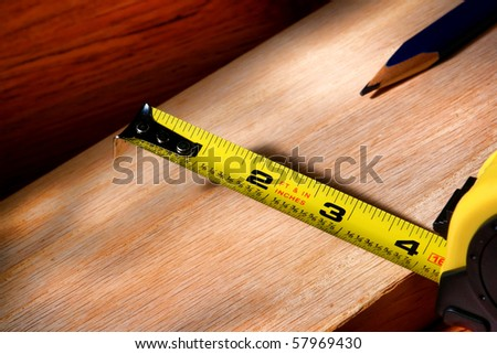 Self retracting construction tape measure and carpenter pencil on wood plank for a custom cabinetry woodworking project in a carpentry workshop - stock photo