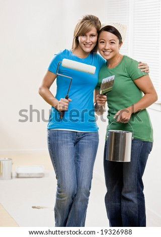 Self-sufficient friends painting with paint roller and paint brush and paint can and renovating home - stock photo