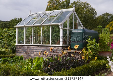 Self sufficient. Greenhouse with a large water collection tank in the UK cottage garden. - stock photo