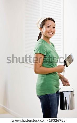Self-sufficient woman painting with paint brush and renovating home - stock photo