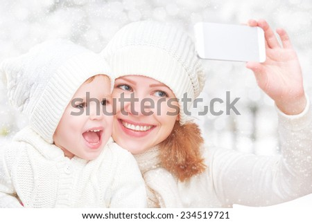 selfe  in winter. happy family mother with baby daughter and photographed self  on a mobile phone - stock photo