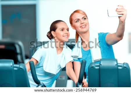 Selfie. Beautiful mature woman bonding her teenage daughter in sports clothing after workout on exercise bicycle in the gym and doing selfie on her smartphone - stock photo