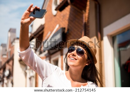 Selfie! Beautiful young funky woman making selfie while standing outdoors - stock photo