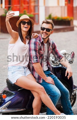 Selfie! Beautiful young loving couple sitting on scooter together and making selfie by their smart phone  - stock photo
