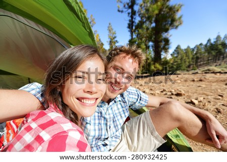 Selfie camping couple in tent taking self portrait using camera smartphone. Campers taking picture smiling happy outdoors in forest. Happy people having fun. Asian woman, Caucasian man. - stock photo