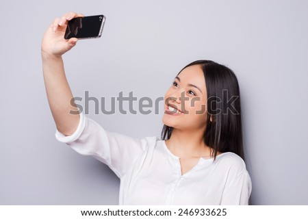 Selfie! Cheerful young Asian woman holding mobile phone and making selfie by her smart phone while standing against grey background - stock photo