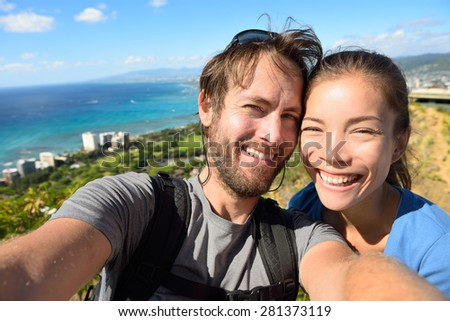 Selfie couple travel fun - Tourists on Hawaii taking selfie photo of Honolulu and Waikiki beach. Woman and man on hike visiting viewpoint lookout in Diamond Head State Monument and park, Oahu, USA. - stock photo