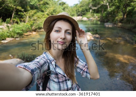 Selfie. Female tourist taking picture of herself with jungle river on the background