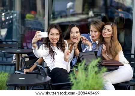 Selfie Four women sitting in a cafe on the street - stock photo