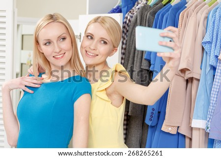 Selfie from the shop. Two smiling girls making a selfie on a phone standing by clothing rack in a store - stock photo