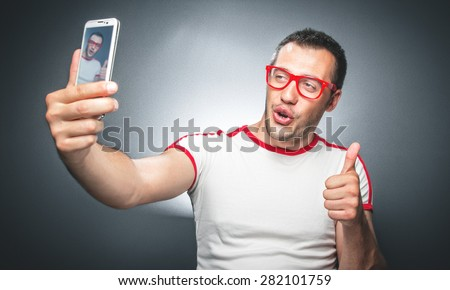 Selfie. Funny man taking a selfie photo, isolated on dark dark gray background. Studio shot - stock photo