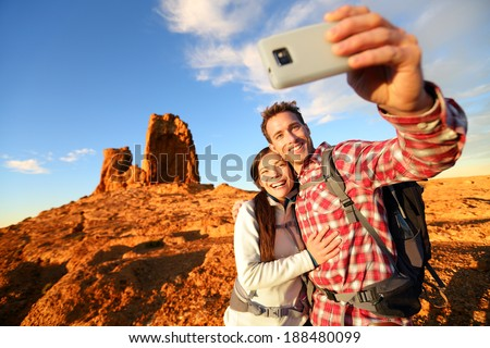 Selfie - Happy couple taking self portrait photo hiking. Two friends or lovers on hike smiling at camera outdoors mountains by Roque Nublo, Gran Canaria, Canary Islands, Spain. - stock photo