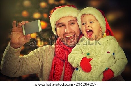 selfie  in Christmas. happy family father dad playing with baby daughter and photographed on a mobile phone