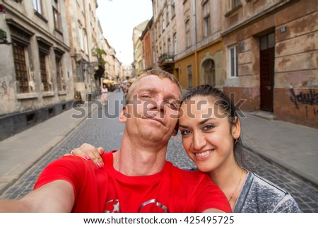 selfie man and woman on the street of Lviv. There are few people on the background - stock photo