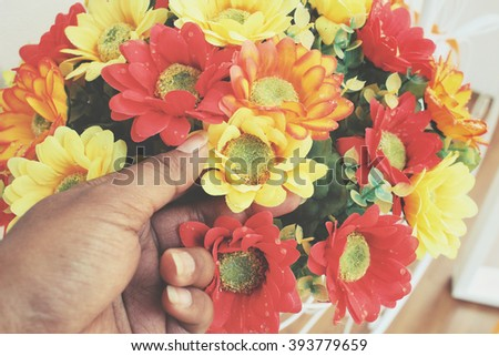 Selfie of artificial flowers with hand