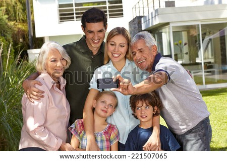 Selfie of family in three generations with children in summer in front of a house - stock photo
