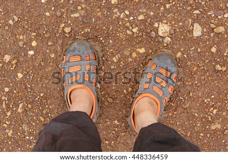 Selfie of feet in rubber shoes on dirt road top view