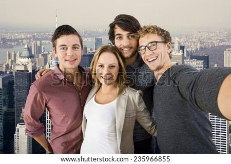 Selfie of four tourist on top of the famous tall building in New York City, with a great view over manhattan - stock photo