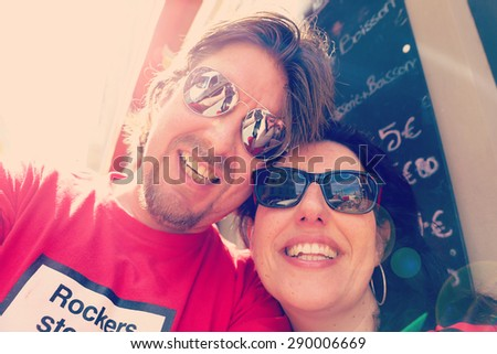 Selfie of happy couple on holidays with filters applied for hipster look - stock photo