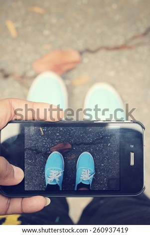 Selfie of shoes with smartphone - stock photo